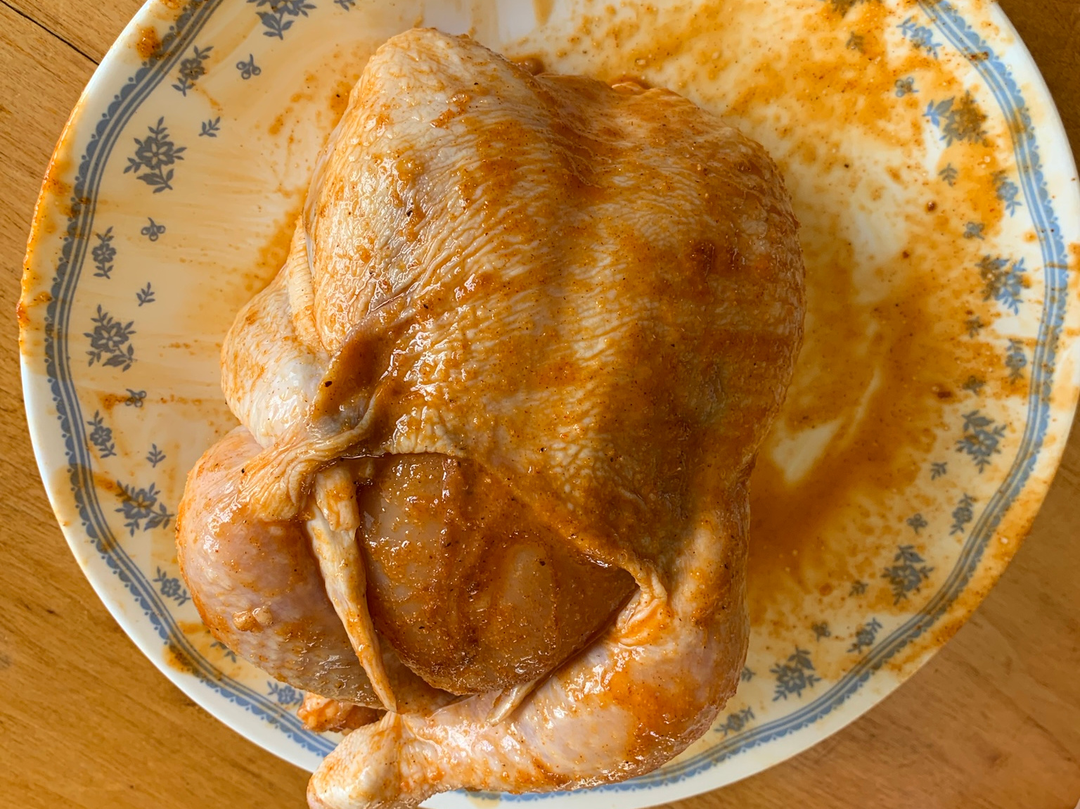 A chicken, rubbed with my homemade rub, ready for cooking.  It's quite yellow, probably from the paprika.