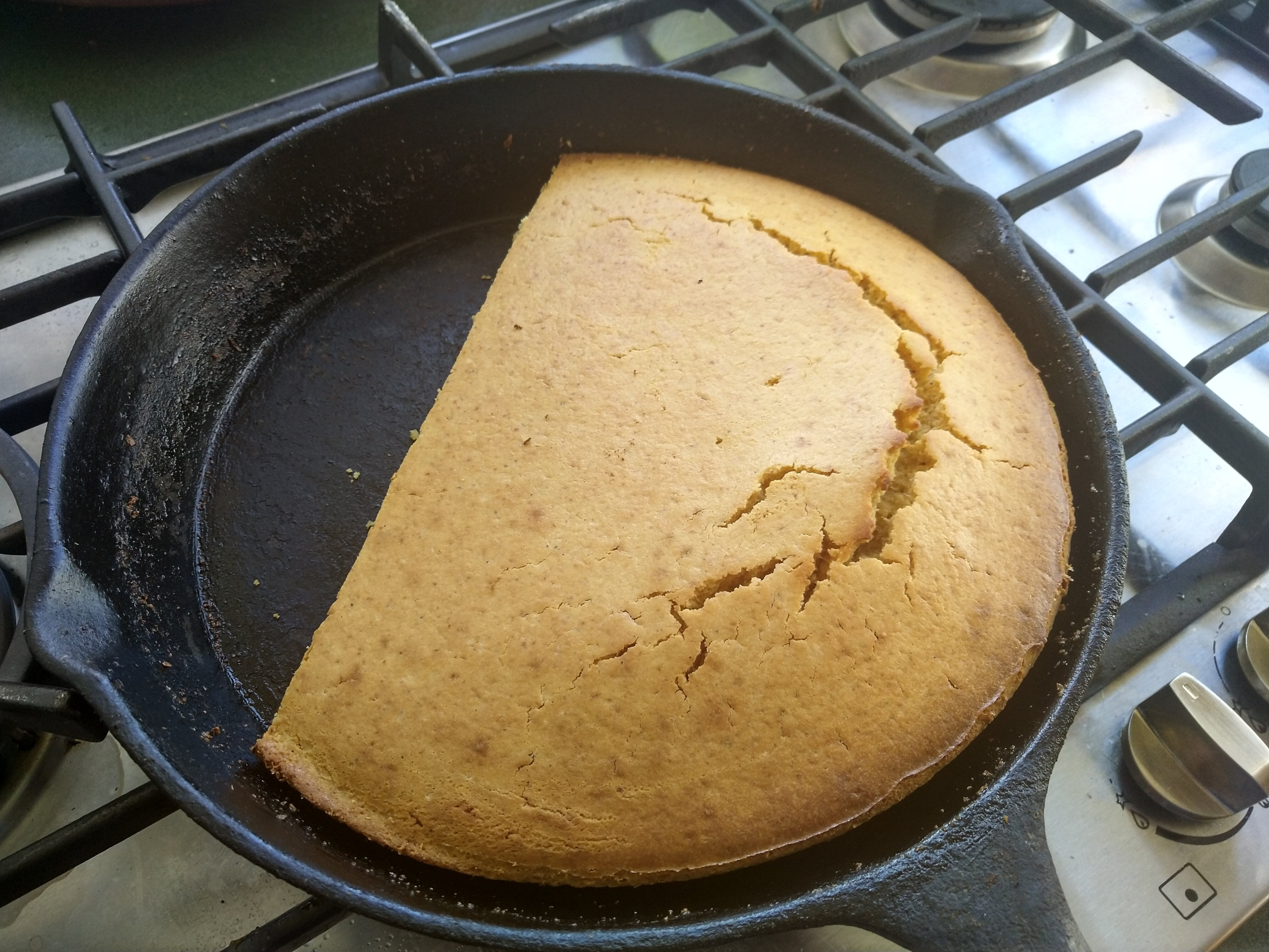 A cast-iron skillet, hot from the oven, cradling a golden-brown cornbread.
