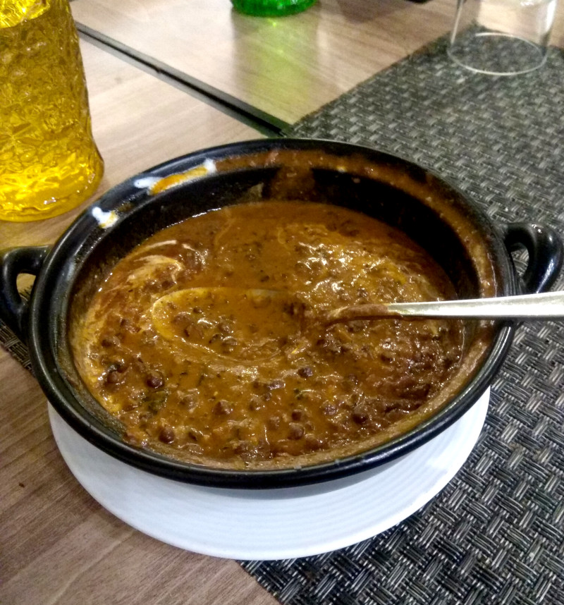 A dark, brown-green daal makhani, with swirls of cream visible.