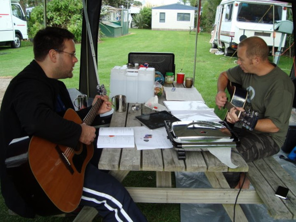 Eric and Russell, playing guitars at a picnic table while out camping