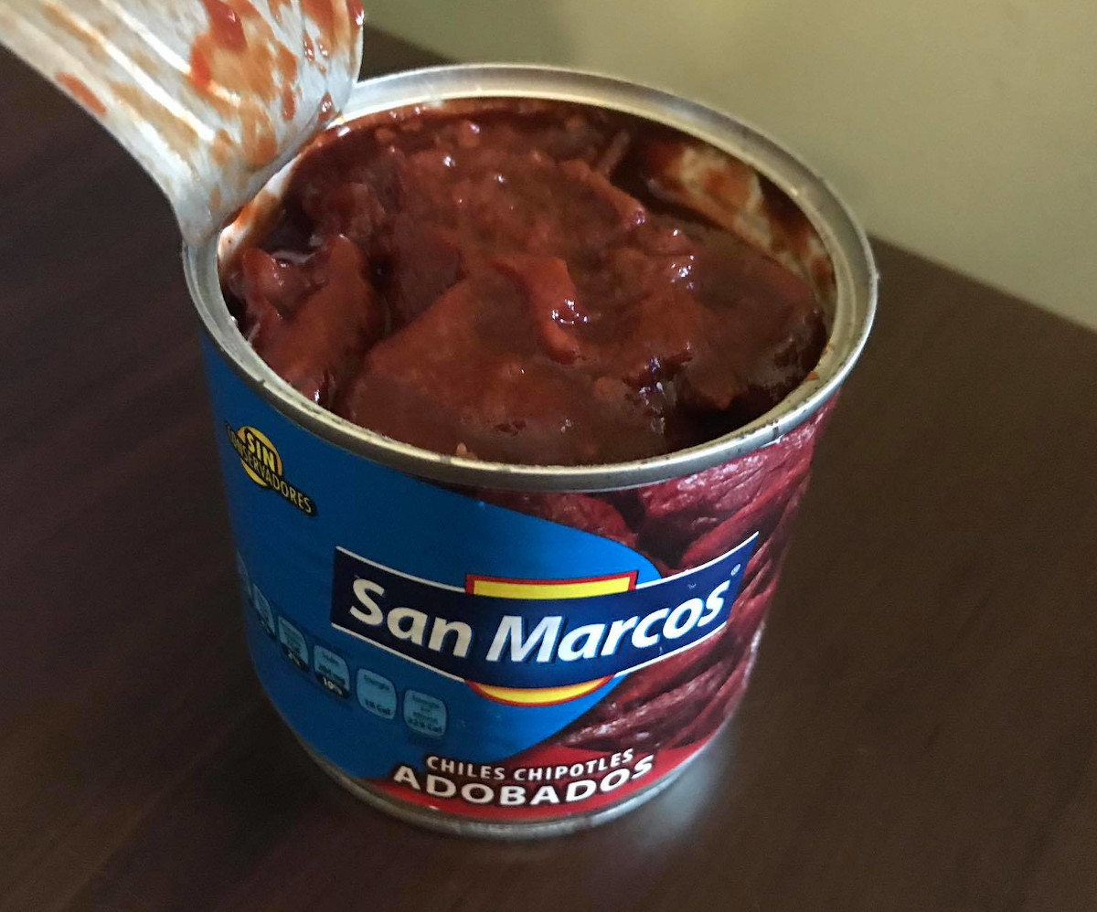 A can of chipotle peppers, opened to show them soaking in rich red-brown adobo sauce